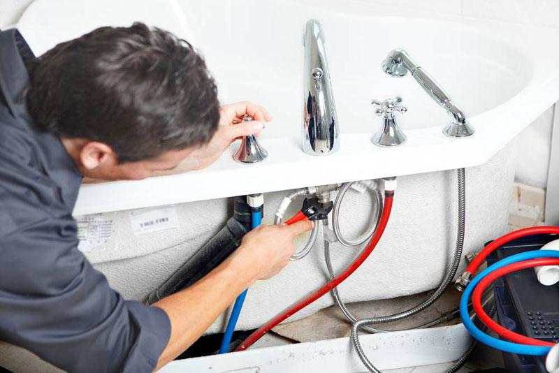 Addetto che lavora su impianto idraulico